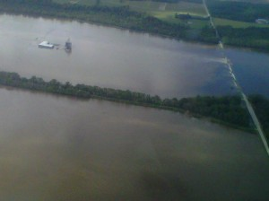 Photo Attachment B - Farm headquarters and grain bins under water near the Black River with water spilling over the nearby highway
