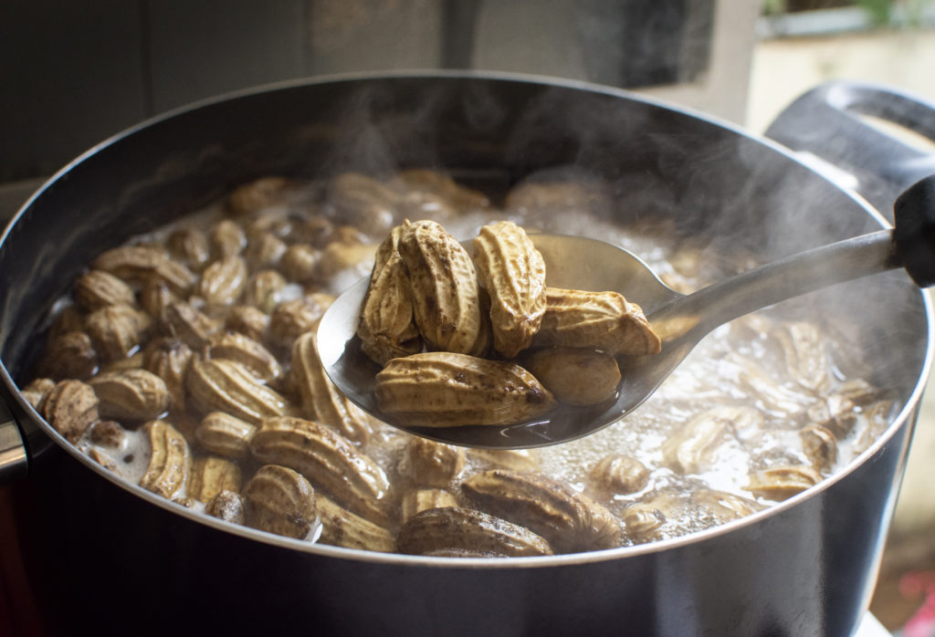 Peanuts boiled in ladle with boiling peanuts as a backdrop.